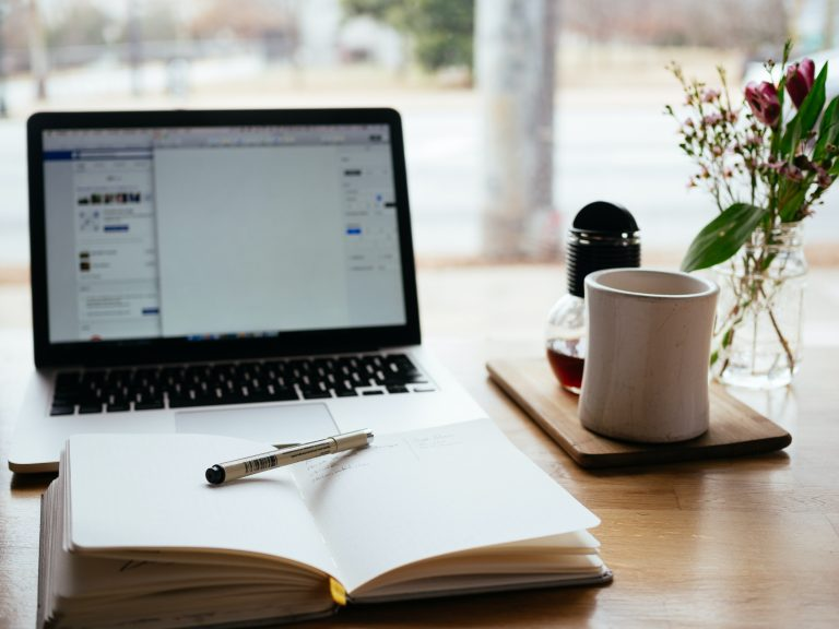 Image of notebook, computer, and coffee.